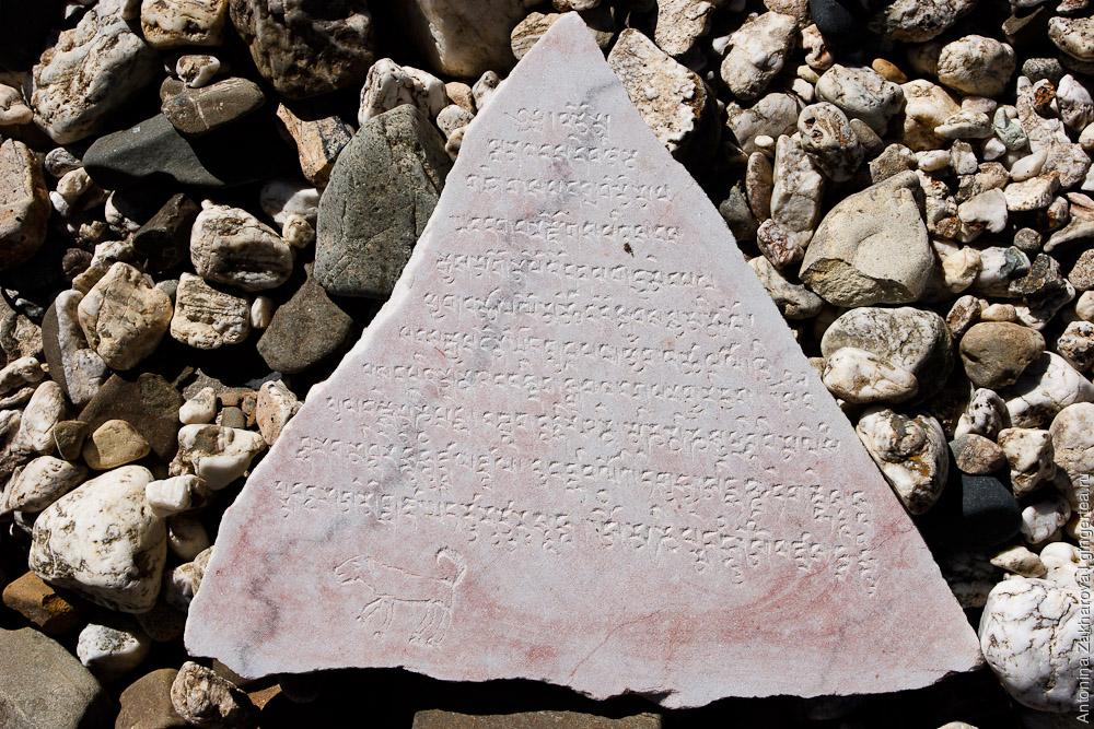тибетские манты, выбитые на околодорожном камне