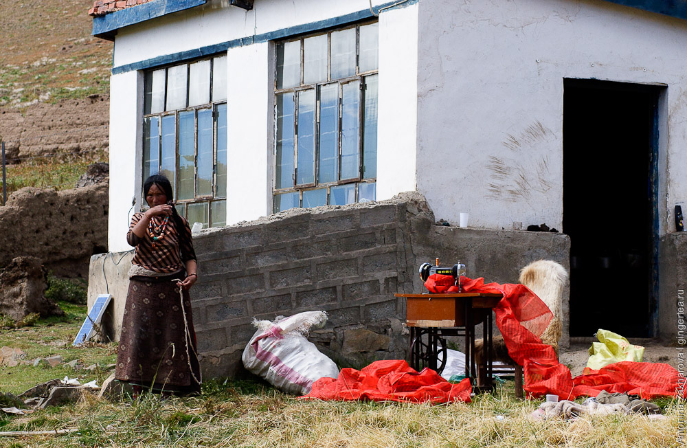 Тибетка шьет молитвенные флажки