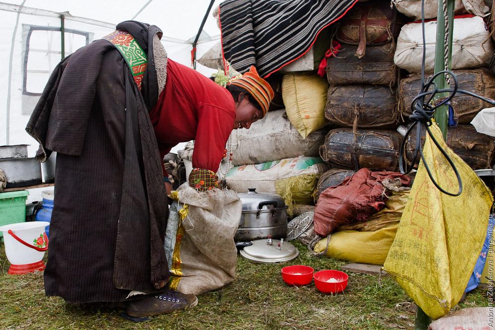 тибетская женщина-кочевница накладывает в миски цампу