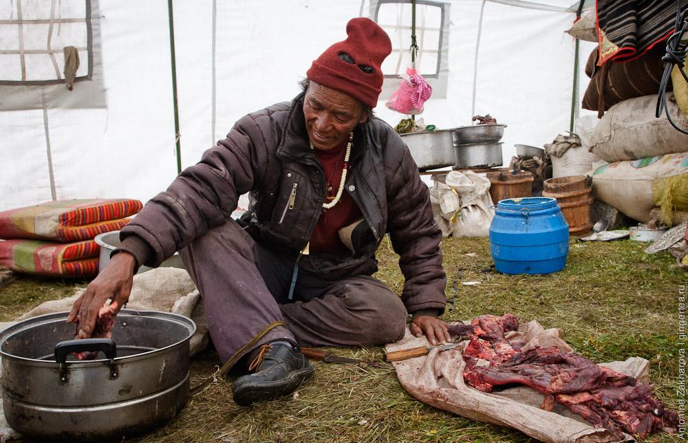 тибетец режет мясо в палатке