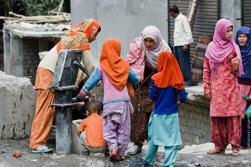 женщины и дети набирают воду из колонки в Каргиле, Индия