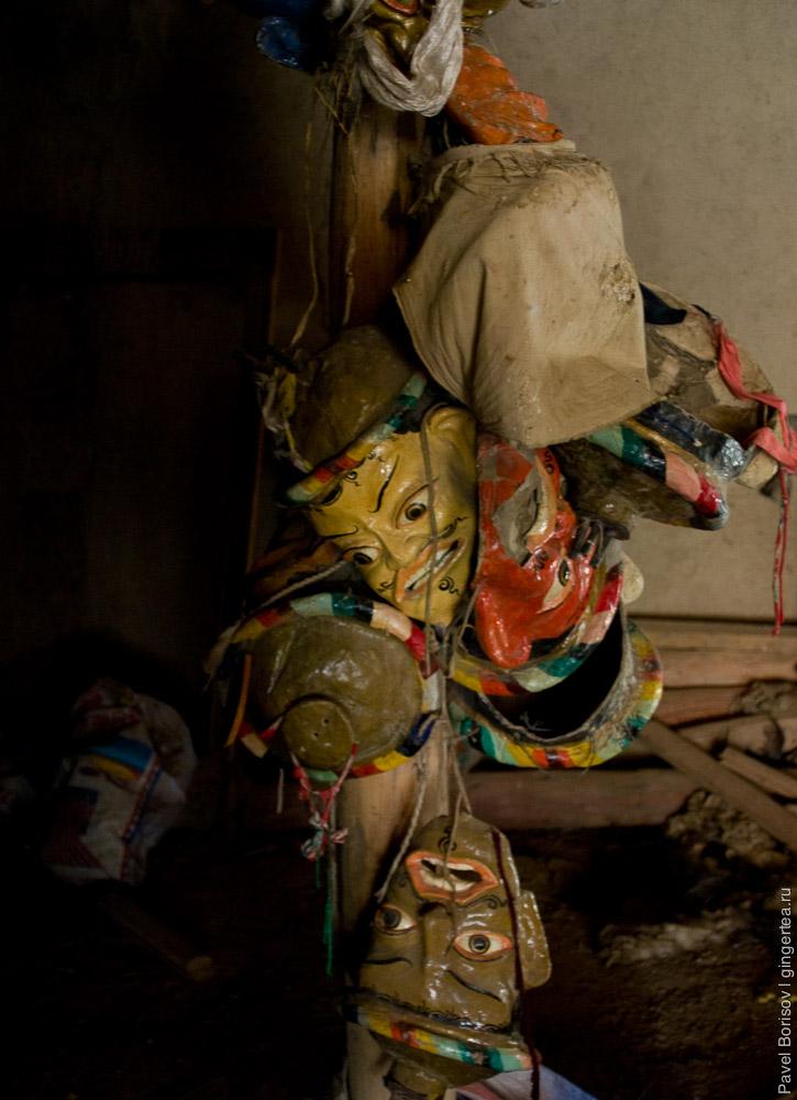 В подсобном помещении висят маски, в которых ламы танцуют во время фестиваля