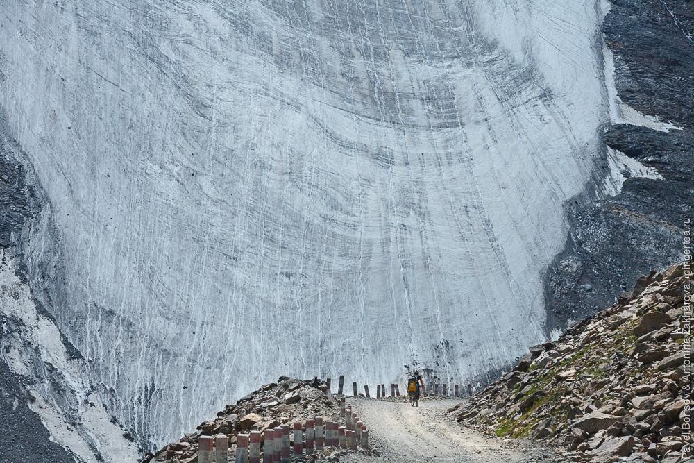 велосипедист едет по горной дороге на фоне ледника в Китайском Тянь-Шане
