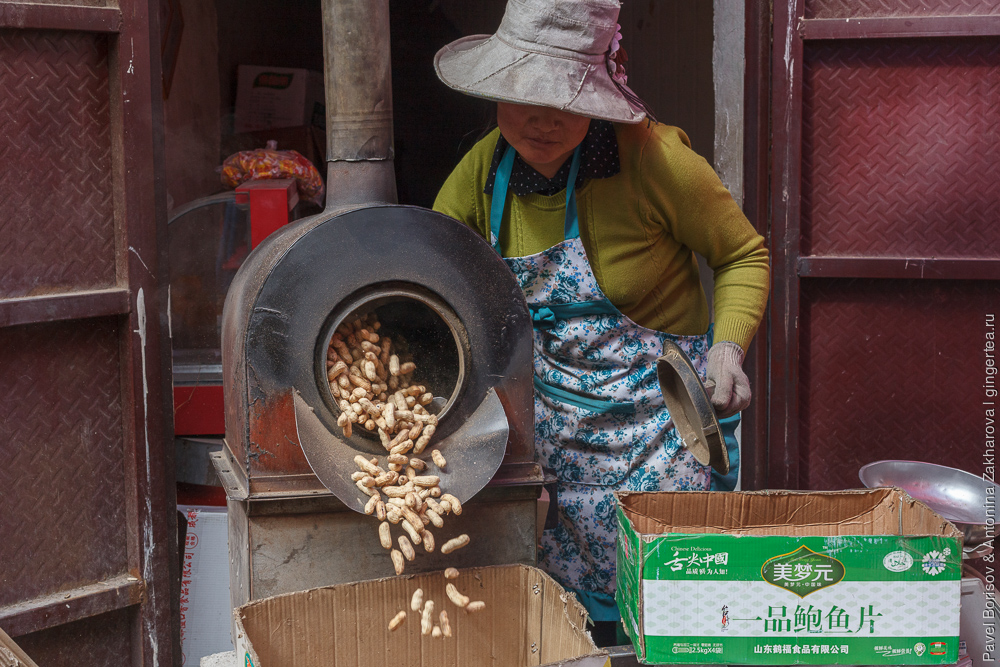 Цзадо, женщина жарит арахис