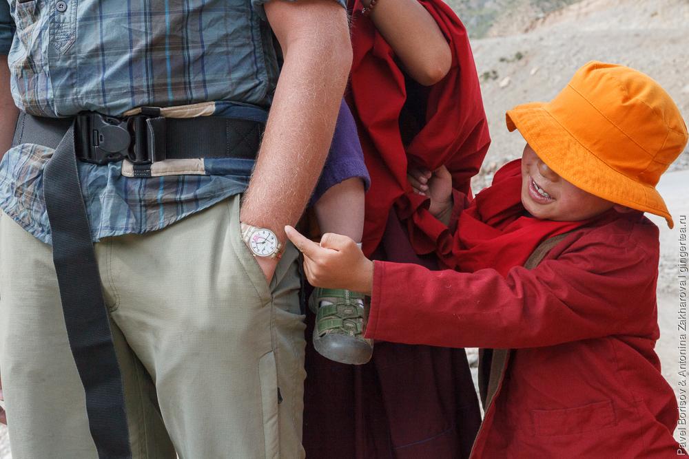 мальчик-монах показывает на волосатую руку европейца