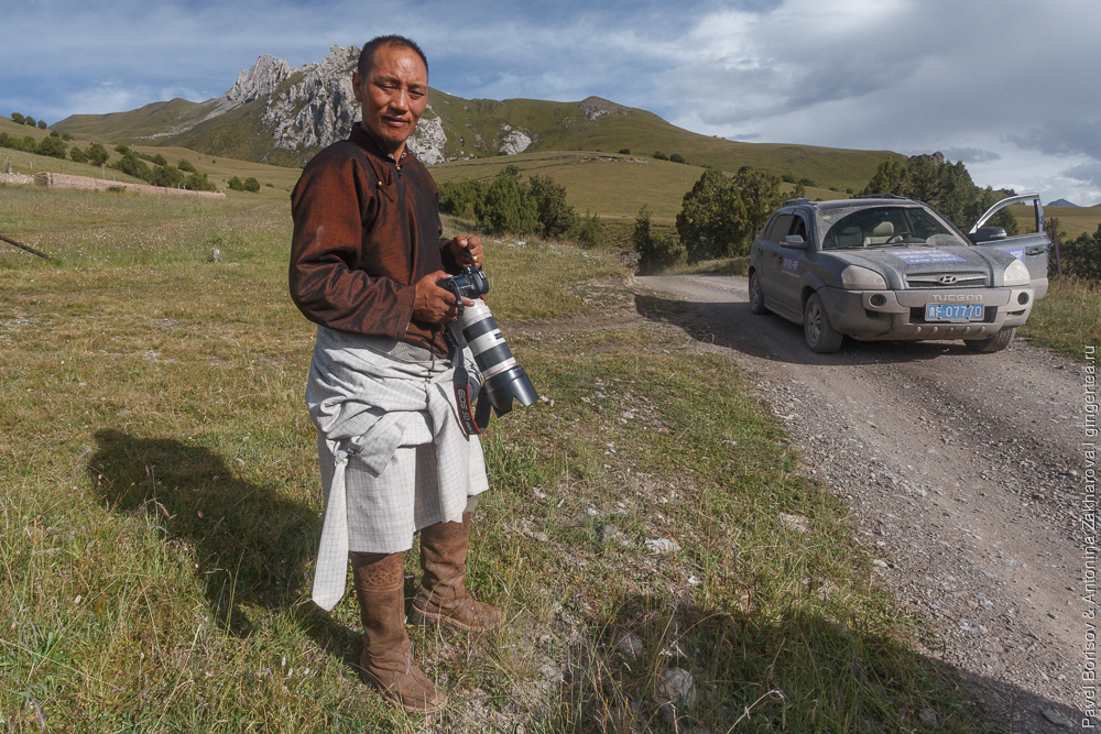 тибетец с фотоаппартом Canon и длиннофокусным объективом
