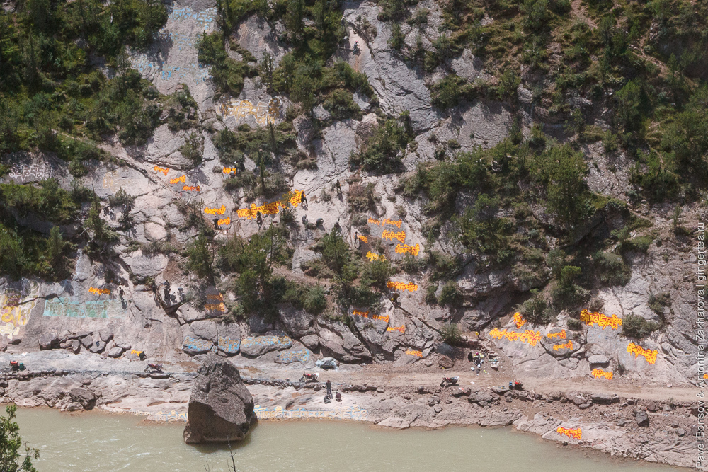 тибетцы высекают мантры на скале