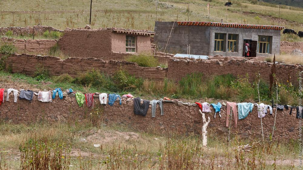 белье сушится на заборе тибетского дома в провинции Цинхай
