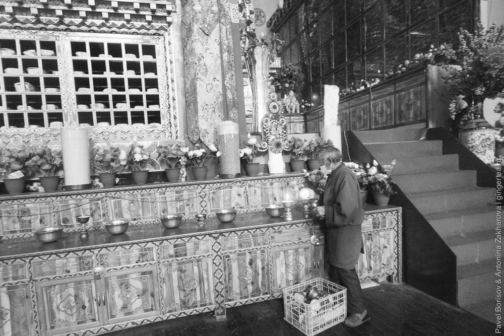Тибетец зажигает масляные лампады