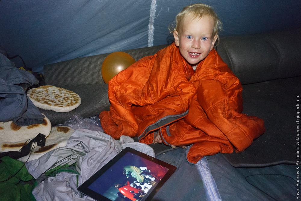 Маленький ребенок в палатке во время дождя