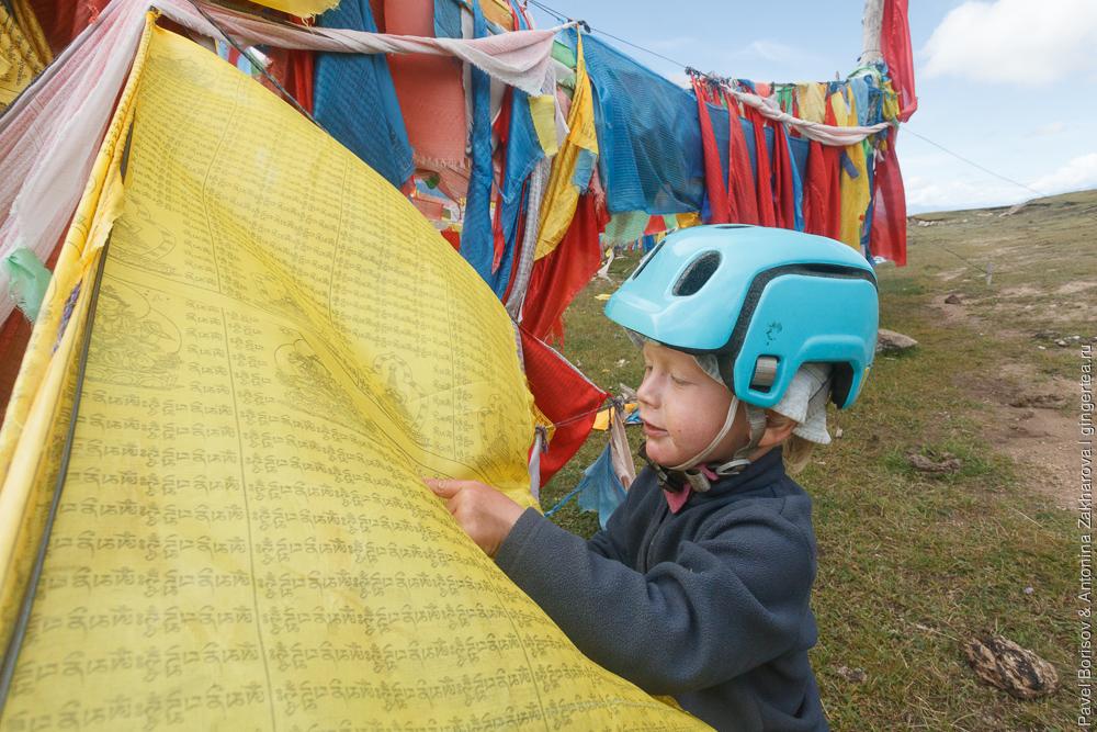 ребенок рассматривает тибетские флажки