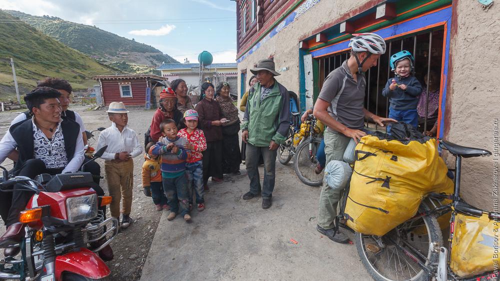 ребенок в велопоходе и тибетцы в традиционной одежде, Сычуань