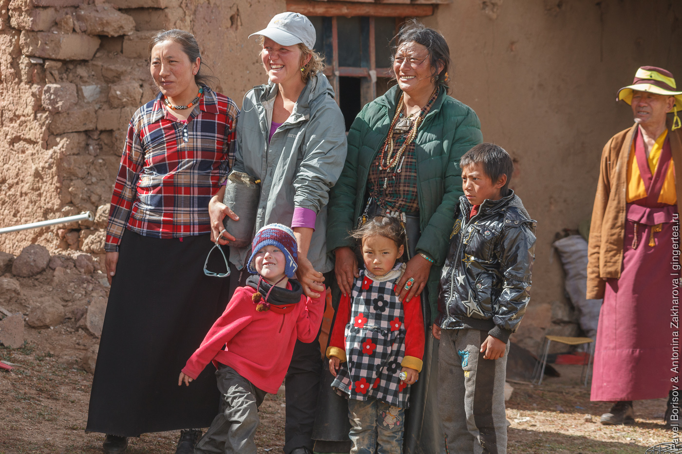 русский велосипедист смеется в компании тибетцев