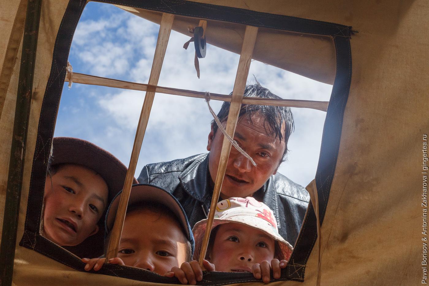 тибетцы заглядывают через окно палатки