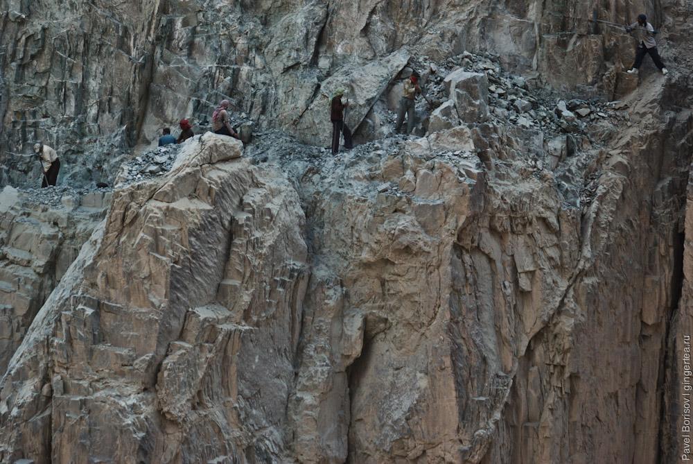 индийские рабочие ломами откалывают куски скалы на строящейся дороге из Леха в Падум