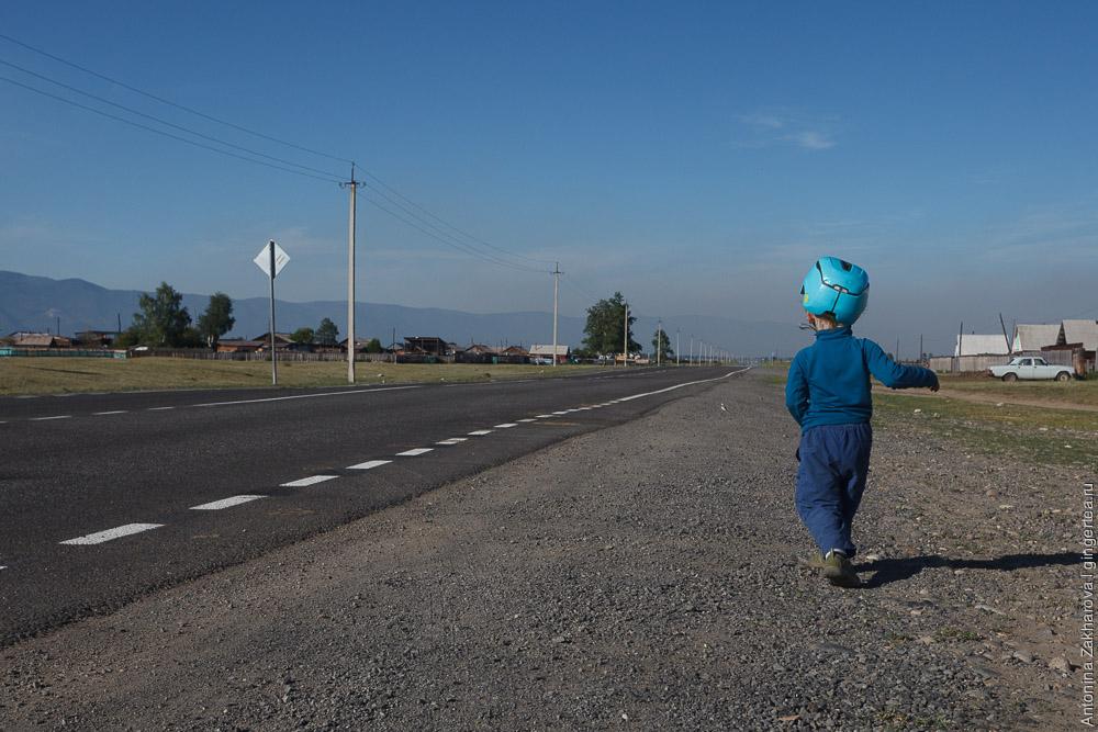 ребенок в велосипедном шлеме идет по дороге в Бурятии